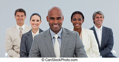 Charismatic Ethnic businessman with his team smiling at the...