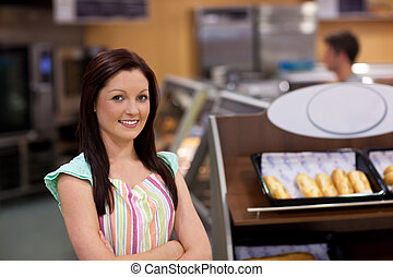 Charismatic female cook smiling at the camera in front of...