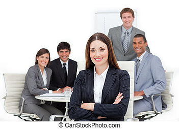 Charismatic female executive sitting in front of her team in...