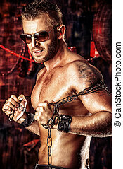 Handsome muscular man with chain in the old garage.