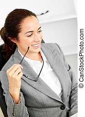 Charismatic hispanic businesswoman holding glasses sitting at her desk in her office