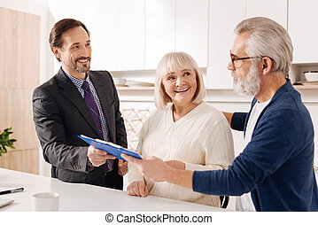 Charismatic lawyer giving consultation to aged couple about purchase
