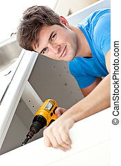 Charismatic man repairing his sink and holding a drill in the kitchen at home