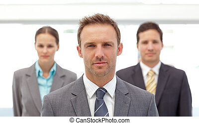 Charismatic manager posing in front of his employees in the...
