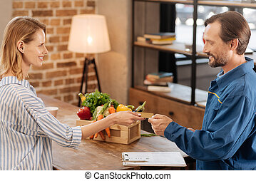 Charismatic modern lady paying for delivery