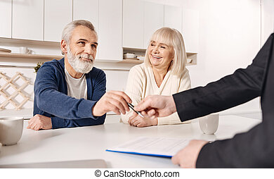 Charismatic old couple signing agreement at home