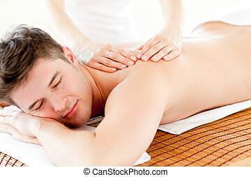Charismatic relaxed man enjoying a back massage in a spa...