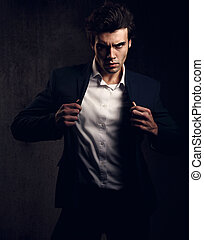Charismatic sexy male model posing and holding the fashion...