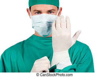 Charismatic surgeon wearing surgical gloves against a white...