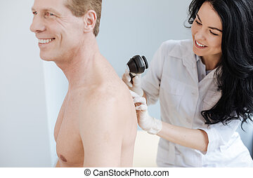 Charismatic young dermatologist using dermatoscope for work in the clinic