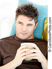 Charismatic young man holding a cup lying on the sofa in the...
