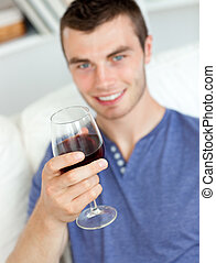 Charismatic young man holding a glass of wine sitting on a sofa in the living-room