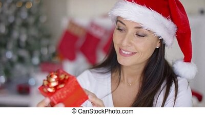 Charismatic young woman holding a Christmas gift
