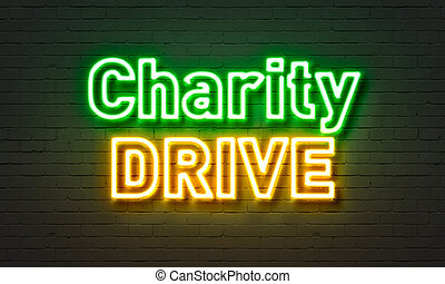 Charity drive neon sign on brick wall background.