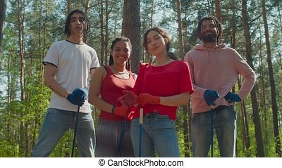 Group of environmental friendly multiracial diverse charity activists in protective gloves with garden tools posing on sunny day in forest. Environmental protection, volunteering and ecology.