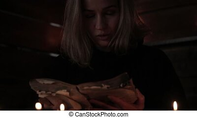 Charlatan witch reading book of black magic, view on burning candle. magic ritual.