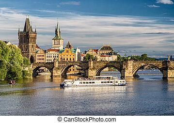 Charles bridge and cruiseship on river Vltava, Prague -...