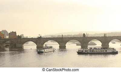 Charles bridge, Prague against the backdrop of a tourist ship at sunset, general plan