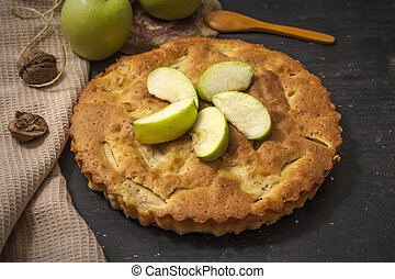 Charlotte apple pie on a black wooden table with slices of green apples