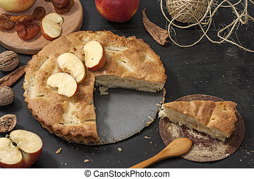 Charlotte apple pie on a black wooden table with slices of red apples