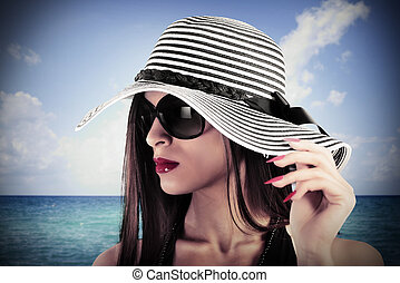 Charm at sea - Elegant woman with hat and sea on background