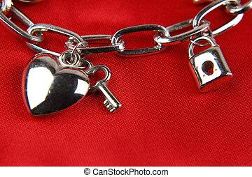 Closeup of heart and key on charm bracelet