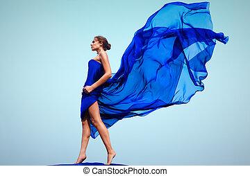 Photo of graceful female folded in dark blue chiffon shawl outside
