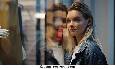 Charmed young blonde woman stands before a show window in the shopping mall