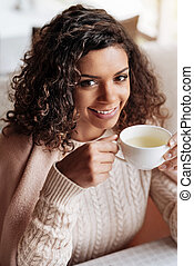 Charming African American woman enjoying the cup of tea