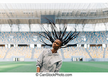 Charming African American woman listening to music on earphones swinging her braided hair at field stadium