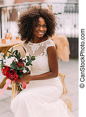 Charming african bride with wedding bouquet in hands cheerfully smiling to the camera