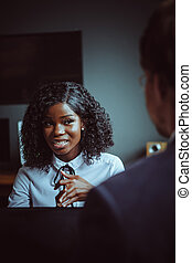 Charming African business woman listens to his male colleague sitting with his back in foreground. Young African American girl portrait. Business meeting concept. Tinted image