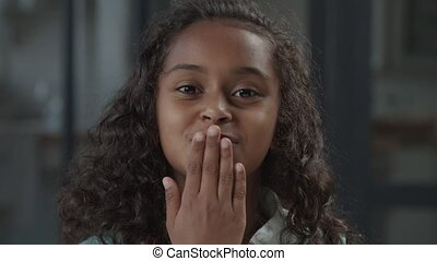 Portrait of charming elementary age african american girl with long curly hair blowing kisses, looking playfully with cheerful radiant toothy smile, expressing positivity and happiness.