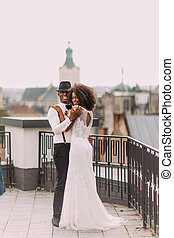 Charming african wedding couple hugging on the terrace with ...