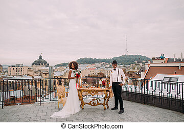 Charming african wedding couple on the terrace with amazing view on ancient Lviv architecture