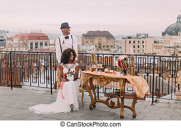 Charming african wedding couple on the terrace with amazing view on Lviv ancient architecture