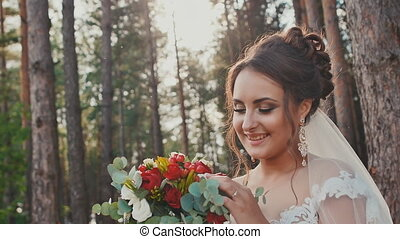 Charming and happy bride in a beautiful wedding dress with a bouquet of flowers in a pine forest in the sun. Wedding day.