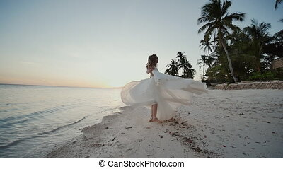Charming and happy bride in a white dress dancing barefoot on the sandy shore of a tropical beach. Ocean. The palms. Sunset.