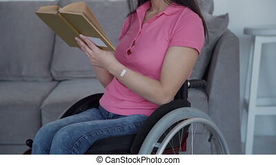 Adult woman in wheelchair reading book at home - Charming...