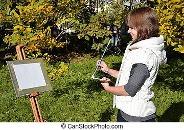 Charming artist in a park - Pretty female artist drawing...