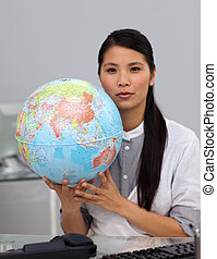 Charming asian businesswoman holding a globe