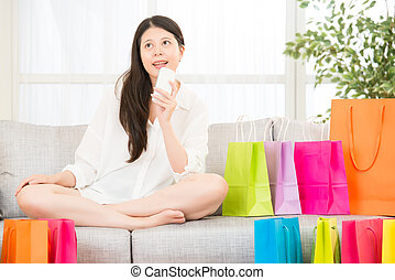 asian woman thinking shopping online with smartphone
