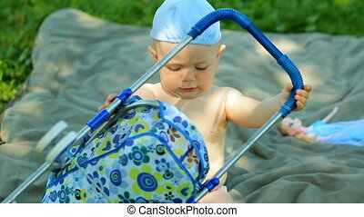 Charming baby boy playing in the garden with a small doll and stroller