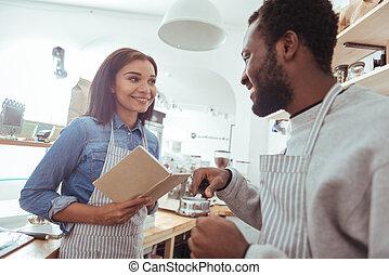 Charming barista explaining his colleague how to use portafilter