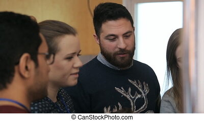 Charming bearded man discusses working project with his colleagues.