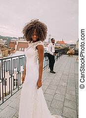 Charming black bride in vintage lace dress on the rooftop. Confident stylish groom on background