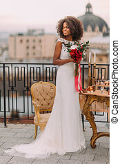 Charming black bride with wedding bouquet in hands standing on the terrace