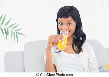 Charming black haired woman in white clothes drinking orange juice in a living room