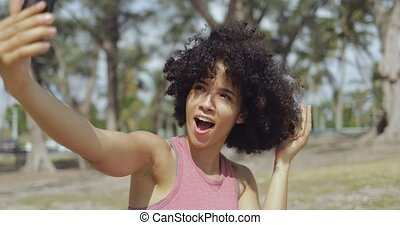 Charming black woman posing for selfie in park