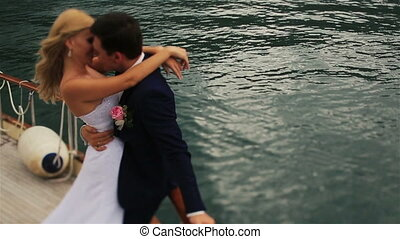 Charming blond bride and handsome groom passionately kissing  on the yacht with the mountains and sea on background